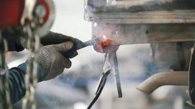 El ` s del mecánico da a reparación la pieza del ` s del coche con un soldador del gas metrajes