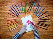 El ` s del niño da el dibujo de una flor en un cuaderno con los lápices del color en la tabla de madera Imagen de archivo