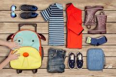 El ` s del niño da la mudanza de una maleta al lado de la ropa en el piso Imagen de archivo libre de regalías
