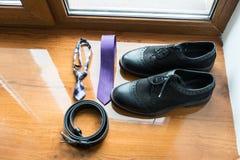 El ` s del novio y dog's que se casan los accesorios Corbata de la lila y zapatos de cuero negros del correa y negros en un fon Foto de archivo libre de regalías