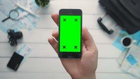 El ` s del viajero de la opinión superior del concepto que viaja da sostener el teléfono vertical con los puntos verdes de la pan almacen de video