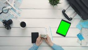 El ` s del viajero de la visión superior da la comprobación del dinero y boleto y tableta digital con la pantalla verde que mient metrajes