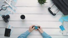 El ` s del viajero de la visión superior da la mirada del mapa del mundo usando smartphone en el escritorio de madera blanco almacen de metraje de vídeo