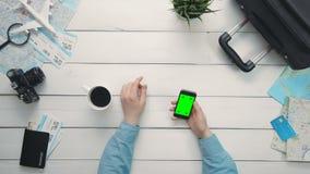 El ` s del viajero de la visión superior da mostrar gestos múltiples usando smartphone con la pantalla verde en el escritorio de  metrajes