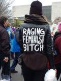 El ` s marzo en Washington DC, mujer de las mujeres que caminaba a través de la muchedumbre que llevaba una chaqueta etiquetó ` f Fotos de archivo libres de regalías
