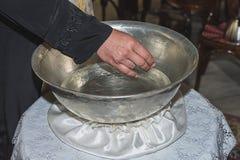 El sacerdote bendice la fuente bautismal del bautizo llenada de agua santa en la iglesia durante la ceremonia Imágenes de archivo libres de regalías