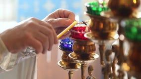 El sacerdote enciende el fuego en las lámparas almacen de video
