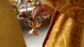 El sacerdote enciende incienso en el incensario almacen de video