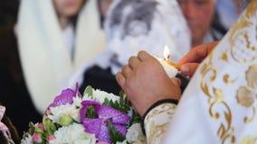 El sacerdote enciende la vela al novio almacen de video