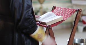 El sacerdote lee la biblia o el libro de oración metrajes