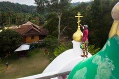 El sacerdote ortodoxo restaura cruces en las bóvedas de la iglesia Fotografía de archivo