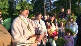 El sacerdote pagano canta canciones populares con la audiencia pública Gente alrededor de la chimenea almacen de metraje de vídeo