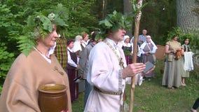 El sacerdote pagano con el palillo y el roble deja la guirnalda en la charla principal a la gente almacen de video