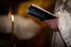 El sacerdote sostiene la biblia Imágenes de archivo libres de regalías
