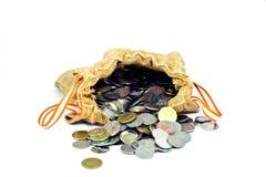 El saco de la arpillera por completo de monedas y la pila de monedas salen Fotografía de archivo