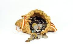 El saco de la arpillera por completo de monedas y la pila de monedas salen de saco Fotografía de archivo