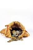El saco de la arpillera por completo de monedas y la pila de monedas salen de saco Imágenes de archivo libres de regalías