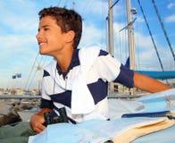 El sailorsitting adolescente del muchacho en correspondencia de la carta del barco del puerto deportivo Imagenes de archivo