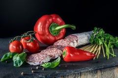 El salami con paprika roja, los tomates y la pimienta en la pizarra suben imagen de archivo