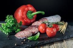 El salami con paprika roja, los tomates y la pimienta en la pizarra suben fotos de archivo