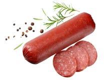 El salami fum? la salchicha con las rebanadas, el romero y los granos de pimienta aislados en el fondo blanco Visi?n superior imagen de archivo libre de regalías