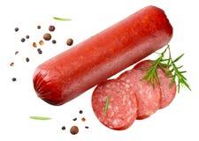 El salami fum? la salchicha con las rebanadas, el romero y los granos de pimienta aislados en el fondo blanco Visi?n superior imagen de archivo