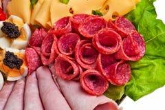 El salami rueda en el plato, primer. imagen de archivo