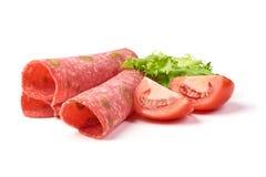 El salami tradicional de las rebanadas fum? la salchicha, combinada con la aceituna verde, aislada en el fondo blanco foto de archivo