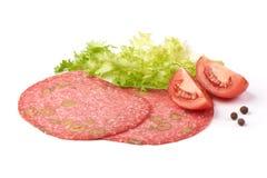 El salami tradicional de las rebanadas fum? la salchicha, combinada con la aceituna verde, aislada en el fondo blanco fotos de archivo libres de regalías