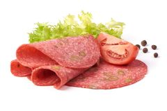 El salami tradicional de las rebanadas fum? la salchicha, combinada con la aceituna verde, aislada en el fondo blanco foto de archivo libre de regalías