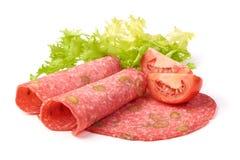 El salami tradicional de las rebanadas fum? la salchicha, combinada con la aceituna verde, aislada en el fondo blanco imágenes de archivo libres de regalías