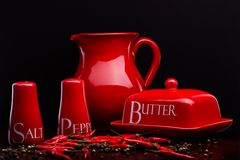 El salero, el pimentero, la mantequilla y la jarra rojos fijaron en fondo oscuro de Cristina Arpentina Fotografía de archivo