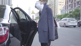 El salir bien vestido serio del muchacho del coche y el caminar abajo de la calle Paisaje urbano urbano en el fondo Joven metrajes