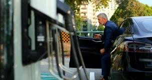 El salir del hombre de negocios del coche en la estaci?n de carga 4k almacen de metraje de vídeo