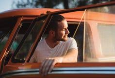 El salir del hombre joven de un coche en un roadtrip a través de campo imágenes de archivo libres de regalías