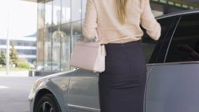 El salir femenino acertado del abogado del coche y el caminar al edificio de oficinas metrajes