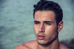 El salir hermoso del hombre joven del agua con el pelo mojado Foto de archivo libre de regalías