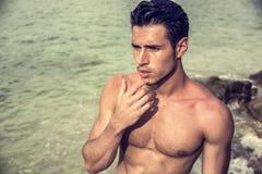 El salir hermoso del hombre joven del agua con el pelo mojado Foto de archivo