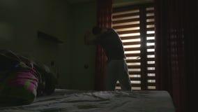 El salir hermoso joven del hombre de la cama por la mañana y la apertura cubre almacen de video