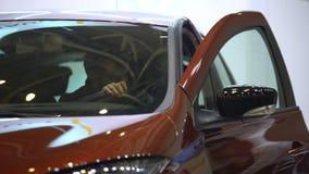 El salir masculino del conductor del coche y fijación de la puerta en el estacionamiento, transporte metrajes