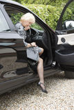 El salir mayor del conductor y del bolso de la mujer del coche Imagen de archivo libre de regalías