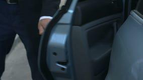 El salir personal del chófer del coche y de la puerta de abertura a su jefe, servicio almacen de metraje de vídeo