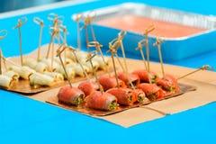 El salmón rueda con los pinchos de la espinaca y del bambú en fondo azul imagen de archivo libre de regalías