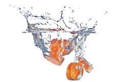 El salpicar abstracto de la zanahoria roja en el agua clara foto de archivo libre de regalías