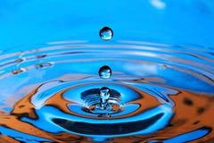 El salpicar anaranjado azul del descenso del agua Foto de archivo libre de regalías
