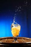 El salpicar anaranjado en el vidrio de agua Imagenes de archivo