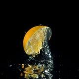 El salpicar anaranjado fuera del agua imagen de archivo