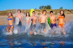 El salpicar corriente de la playa del grupo adolescente de las personas que practica surf Foto de archivo libre de regalías