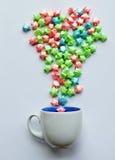 El salpicar de papel de la estrella colorida de la taza de café en el fondo blanco Fotografía de archivo libre de regalías