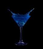 El salpicar en martini azul en negro imagenes de archivo